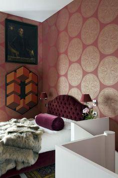 Interesting bedroom, gorgeous deep burgundy tufted headboard. Odd cube painting