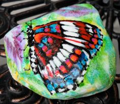 titled: Butterfly Rock. Just over 3 across A pretty butterfly alights upon a lavendar flower. Coated in high gloss sealer to protect paint job beneath.