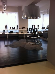 A white lacquered floor leads to dark stained hardwood (and a SICK light fixture) in the Vince Camuto showroom.