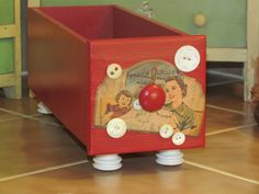 sewing machine drawer, now a cute cubby or box for storage, painted red, with a decoupage sewing needle package image and real buttons, feet are electric fence insulators