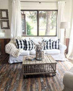 Looks so comfy, and gorgeous. The warmth of rustic wood against white in this living room. Chicken coop coffee table featured.