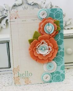 I created a card with layers of felt flowers made with pti flower dies stitched together and stacked felt buttons arranged from top to bottom mimicking the garland.  Background is stamped with rosie posie.