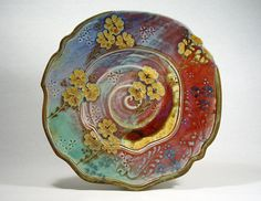 John Calver. Decoration was applied to the platter at the leatherhard stage using clay stamps and trailed and sponged slip. Several glazes, containing copper, cobalt, iron, and rutile, were poured over the surface and allowed to overlap each other.