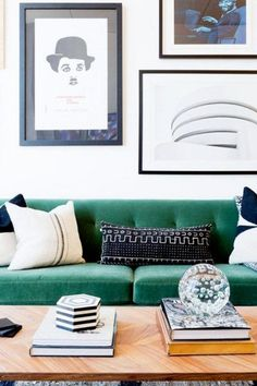 Living room with a monochrome gallery wall and a green velvet sofa