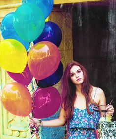 girl. long hair. colorful. being carried away by ballons