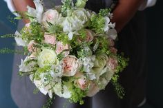 Relaxed and natural bridal bouquet in a fresh green, pale pink and ivory colour palette. Garden Roses, fresh herbs and green bell