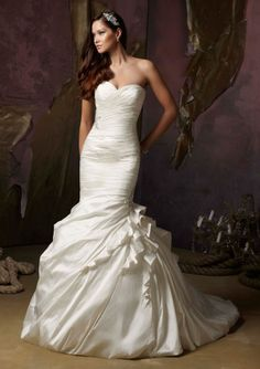 Gorgeous and thrilling to see is Angelina Faccenda 1247 wedding gown in luxurious silk shantung! The mermaid style gown is uniquely beautiful and it offers a ruffled one shoulder strap that crosses the bust line diagonally or it can be removed to show a strapless sweetheart neckline. There are sparkling crystal appliques at the gown's right waist and at the outer thigh on the left. #timelesstreasure
