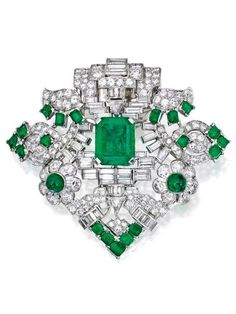 An Art Deco Platinum, Emerald and Diamond Clip-Brooch, Seaman Schepps. Centring an emerald-cut emerald within a fanciful floral frame set with emerald-cut and cabochon emeralds, accented by round, baguette and triangle-shaped diamonds, signed Seaman Schepps