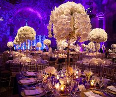 Purple lighting transforming this white and gold wedding reception into a fantastic space.