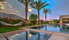Surrounded by lush landscaping and towering signature palm trees, the backyard offers an exquisite oasis featuring an approximately 50-foot zero edge pool with Abalone Pebble Tec finish.