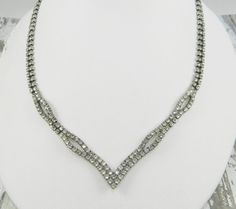 Elegant vintage rhinestone necklace, featuring crystal clear round cut rhinestones that are prong set in a silver tone finish. The necklace is 16 long with a 1 drop. All stones are present & sparkly, with minimal darkening or discoloration to some stones. Surface wear to stones and finish is very minimal, necklace is in good vintage condition. Please look closely at photos as they are the best indication of condition. Thank you for stopping by! :) Group RO