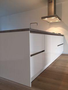 Eiland afzuigkap met plasma systeem boven een hoogglans witte greeploze keuken met keramiek werkblad, beton-look. www.eigenkeuken.nl