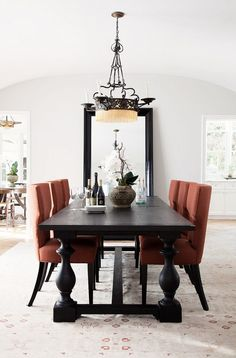 Beautiful dark dining table with a pop or color in the chairs. Also like the use of the leaning mirror.