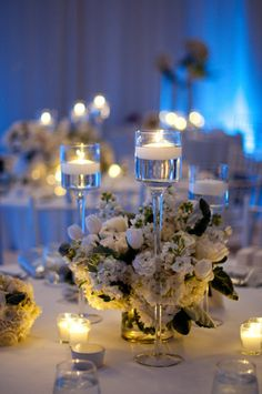 tall trio of stemmed candle holders with lush low arrangement in ...