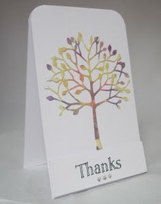 By Linda. Ink white cardstock by sponging on dye ink or by dabbing on Distress Stains. Then die cut a shape -- here the Memory Box arboscello tree.