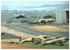 """South African Mirage flying over DC-3s at an airfield"""
