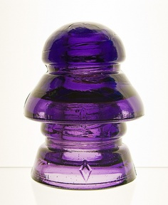 CD 190-191, DIAMOND, Royal Purple  A style of insulator known as a two-piece transposition. This insulator was made by the Diamond Flint Glass Company Ltd of Montreal, Quebec (1903-1913). They were used on open wire telephone lines in the prairies of Saskatchewan, Canada.   Transposition style insulators were made with two or more wire grooves to allow the telephone lines to cross over each other once every several poles. This twisting of the wires would cancel out the interference or…
