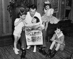 John Wayne reads the comics with his children.