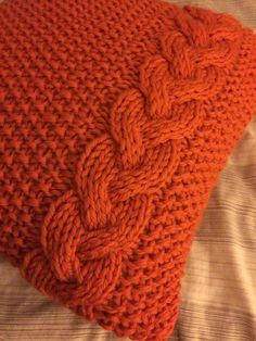 A moss stitch and braided cable pillow cover knit in super chunky yarn.