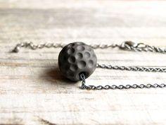 Handmade black ceramic sphere necklace. Antique silver color chain. Textured ceramic. €15,00, via Etsy.