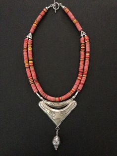by Luda Hunter | A double strand necklace of Vulcanite trade beads from Africa.  The focus of the necklace is an old silver Tuareg crescent triangle pendant I found in Morocco and I added a silver Moroccan bead at the base. The double strand of Vulcanite is held at the shoulder with a 2-hole silver bead which then goes to a single strand at the back of the neck. Finished with 9.25 sterling silver clasp. | 233$