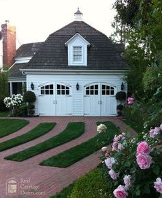 Carriage door garage in white. Love the height, dormer, shingles, brick driveway with green grass divisions, and nearby flowers. So lovely!