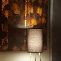 COMPAS : Design d'une lampe, abat jour coton, pied en métal, posée devant un tableau de Jean Serolle.