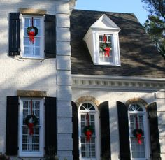 Pop wreaths out each window and close the window on the ribbon to make it stay put--easiest way to decorate your entire house in a flash with no ladder needed! Makes the house look festive during daylight hours, too!
