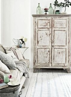 This is amazing example of shabby chic design. The highly distressed wardrobe oozes character, while the soft sofa and painted wooden floor are welcoming and cozy.