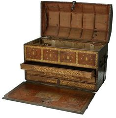 This is a particularly fine example of a travelling coffer, or trunk. The outside of the trunk would originally also have been covered in leather, making it waterproof. Travelling trunks dating from earlier centuries were plain inside with perhaps two small drawers. By the16th century the interiors of expensive trunks for documents or small objects were fitted with many trays and drawers. Some, like this one, had a drop front to provide access to the contents.