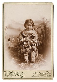 Studio portrait of a little Southern Cheyenne girl. Look at her adorable little toy cradleboard.
