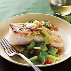Halibut with leeks. Raisins and vinegar lend sweet-tart appeal to a dish inspired by a classic Italian approach.