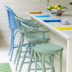 A simple breakfast bar has been brought to life with different bar stool designs painted in a spectrum of pastel shades.