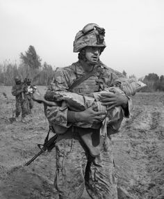 This is a photograph taken by James Nachtwey, in this photo is a soldier holding something in his arms it looks sort of like a dead corpse or it could be worn weaponry.
