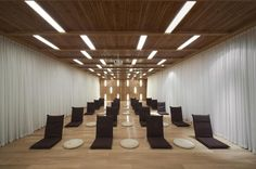 Mediation room with recessed linear lighting.  The way the recessed slotlights span between the beams is very nice.