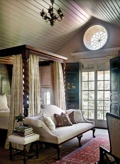 Lanham placed a Chippendale sofa at the foot of a reproduction 19th-century English barley-twist bed. The wrought-iron oculus was originally an attic vent.