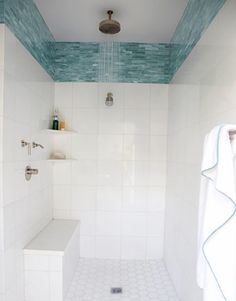 I love the idea of using a neutral color through out the bathroom and then a pretty glass tile strip in a color.  This blue is textured when you look up close.