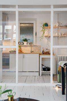 Cuisine blanche, parquet grosses lattes peint en blanc, salle à manger séparée par une verrière atelier.