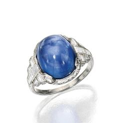 PLATINUM, STAR SAPPHIRE AND DIAMOND RING.  Centered by a cabochon star sapphire weighing approximately 9.75 carats, flanked and framed by numerous old European and baguette diamonds weighing approximately .70 carat, size 5¼. Art Deco or Art Deco style.