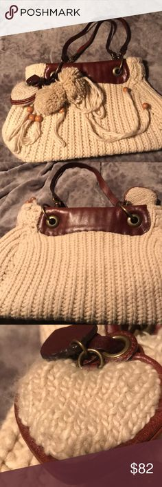 """Juicy Couture Wool and Leather Handbag Unique Juicy knitted handbag.  It is kind of a cream color with brown leather accents.  The hard ware is antique brass.  It has two shoulder straps, a yarn bow on the front, 2 Pom poms, and a knitted heart bag charm.  The bottom has 2 heart """"feet"""" and there are 2 interior zip pockets.  This bag has never been used- it's heavy, but Fabuuulllousss! A great handbag or diaper bag.  There is no damage, stains, etc. There is some pilling here and there but…"""
