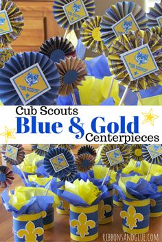 Cub Scouts Blue and Gold Banquet Centerpieces.  made from empty coffee cans, covered  in scrapbooking paper and a Fleur-di-lis die cut.