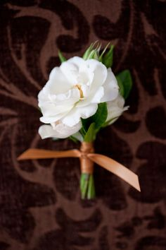 White majolica spray rose blossom and gardenia foliage boutonniere by Sebesta Design. Photo by Liz And Ryan.