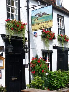 The 16th century The Running Horses pub in   Mickleham's village, Surrey, England, with pub sign of Cadland winning the 1828 Derby