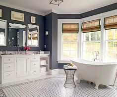 Don't discount dark wall color just yet. Deep gray walls warm this big, bright bath where vintage-inspired tile accents mix light and dark finishes while reflecting personal style. The charcoal paint helps the mostly white space feel more intimate while showcasing elegant embellishments./