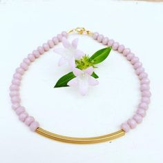 Pale lilac faceted glass rondelle beads strung on flexible wire with a long, gold plated brass tube bead. Clasp and jump ring are gold filled. 8 inches Click here to sign up for the Callaloo mailing l