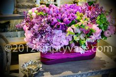 Lilac, ranunculus, hydrangea, tulips, and winter roses in a rounded rectangular glass vase lined with decorative middolina wire.