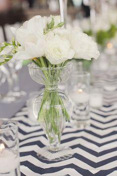 simple floral arrangement as table decor with chevron table runner #weddingreception #tabledecor #weddingchicks http://www.weddingchicks.com/2014/01/29/seaside-wedding-3