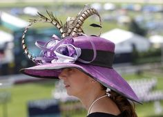 A race fan wears a fancy hat and looks over the grounds before the 138th running of the Kentucky Derby at Churchill Downs in Louisville, Kentucky, May 5, 2012.