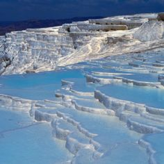 "Pamukkale, meaning ""cotton castle"" in Turkish, is a natural site in Denizli Province in southwestern Turkey. The city contains hot springs and travertines, terraces of carbonate minerals left by the flowing water. It is located in Turkey's Inner Aegean region, in the River Menderes valley, which has a temperate climate for most of the year."