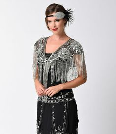 Elegance to remember! Steeped in deco divinity in a 1920s inspired open silhouette, this silver shawl is elaborately beaded and sequined in a delicate sheer black mesh. With a beaded scalloped edging, dripping with beaded fringe, and gorgeous rose details
